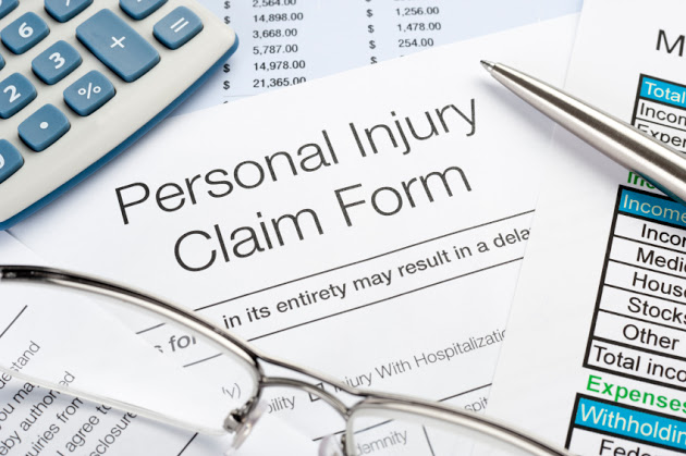 Close up of Personal Injury Claim Form with pen, calculator