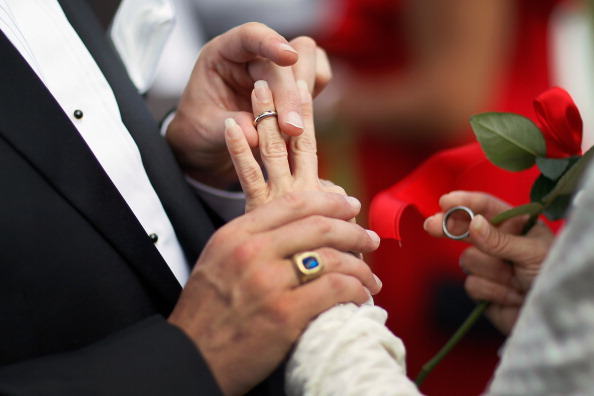 WEST PALM BEACH, FL - FEBRUARY 14:  Paul Cataldo exchanges rings with Tracy Riley during a group Valentine's day wedding at the National Croquet Center on February 14, 2012 in West Palm Beach, Florida. The group wedding ceremony is put on by the Palm Beach Country Clerk & Comptroller's office and 30 couples to tied the knot. (Photo by Joe Raedle/Getty Images)