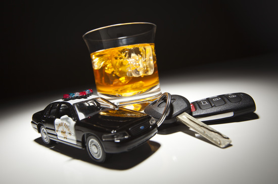 Highway Patrol Police Car Next to Alcoholic Drink and Keys Under Spot Light.